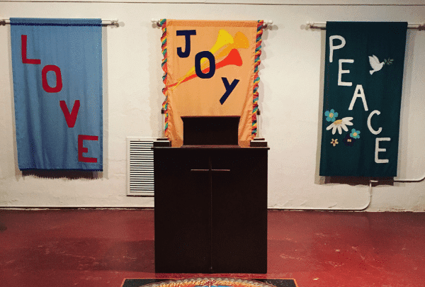 Banners hanging behind a pulpit that read Love, Joy, Peace