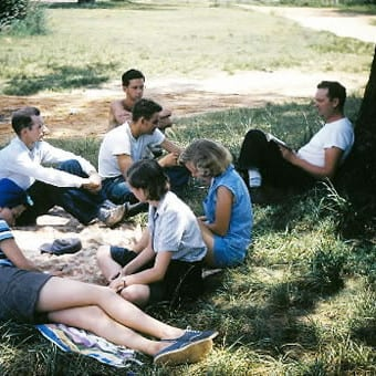 Clarence Jordan and others sitting on the ground under a tree studying
