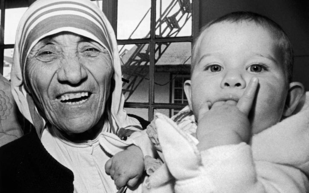 Mother Teresa laughing holding a baby